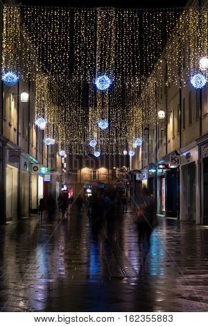 Bath UK - December 19 2016: Christmas lights at Southgate Bath mall. Festive decorations and shoppers at night in modern shopping development of UNESCO world heritage city of Bath
