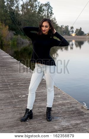 A beautiful fashion model sitting on a bridge in the park.