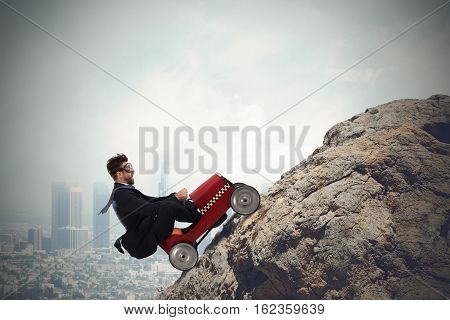 Businessman climb a mountain with a small car. Difficult carrer concept