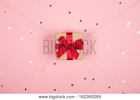 Present with red bow on pink background with tittle sparkles. Flat lay style.