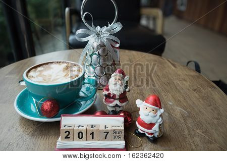 Christmas day and new year Santa Claus hot coffee heart foam on wooden table day time / Christmas coffee