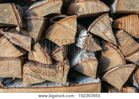 Pile of fresh birch firewood logs on farm.