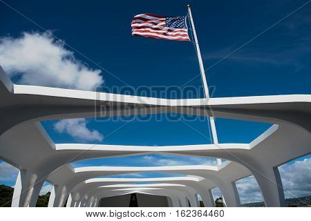 The Star-Spangled Banner flies above the USS Arizona Memorial at Pearl Harbor which the resting place of 1102 of the 1177 sailors and Marines killed on USS Arizona (BB-39) during the Japanese attack on Pearl Harbor on December 7 1941.