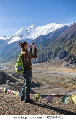 Female tourist photographing landscape on mobile phone during Annapurna circuit trek in Himalayan mountains, Nepal