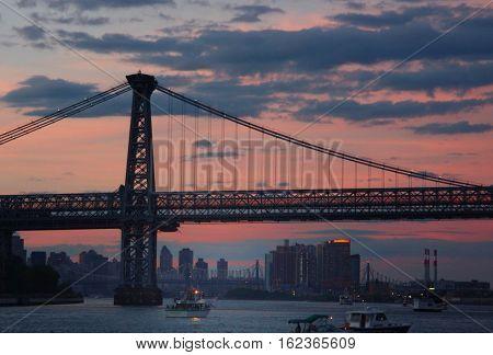 the sun sets over the williamsburg bridge in new york