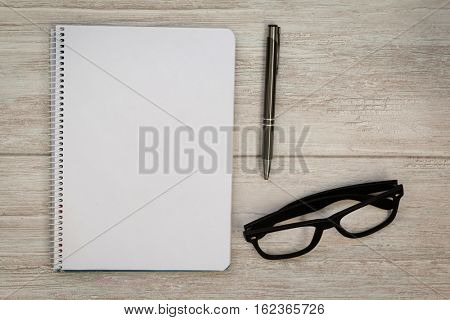 A blank notebook with a pencil and glasses on a grey wooden background