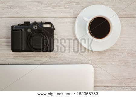 Camera next to a cup of coffee and a laptop on a gray desk