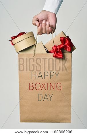 closeup of the hand of a young caucasian man holding a paper shopping bag full of gifts and the text happy boxing day written in it