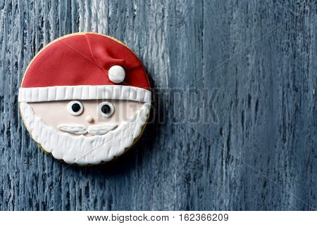 high-angle shot of a christmas cookie in the shape of the face of Santa Claus on a gray rustic wooden surface, with a negative space