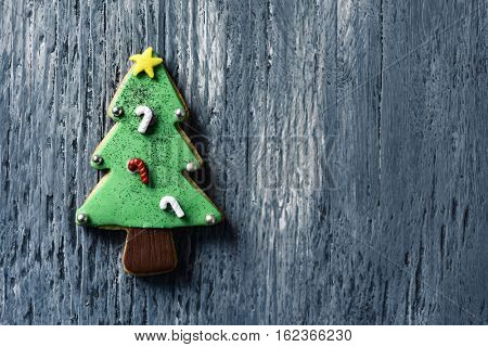 high-angle shot of a christmas cookie in the shape of a christmas tree on a gray rustic wooden surface, with a negative space
