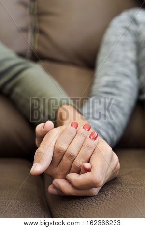 closeup of a young caucasian man and a young caucasian woman holding hands while sitting in a comfortable brown couch