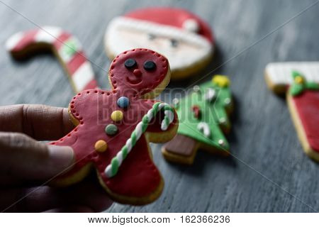 closeup of a young caucasian man with a gingerbread man in his hand and some other of christmas cookies with different shapes and colors on a rustic wooden table