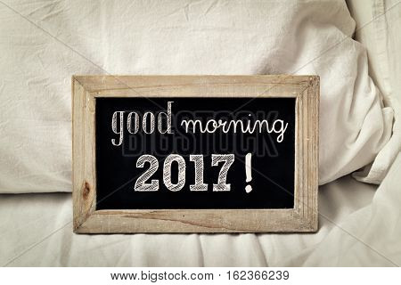 a wooden-framed chalkboard with the text good morning 2017 written in it, placed on a bed set with white bedlinen