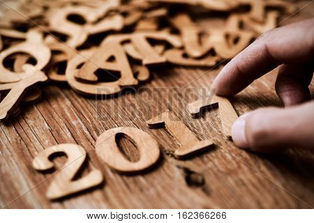 closeup of a young man forming the number 2017, as the new year, with wooden numbers, on a rustic wooden table