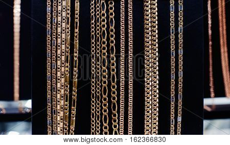 Various golden chains on a black background
