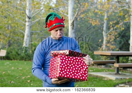Man with sad face holding gifts outdoors wearing a Christmas hat.