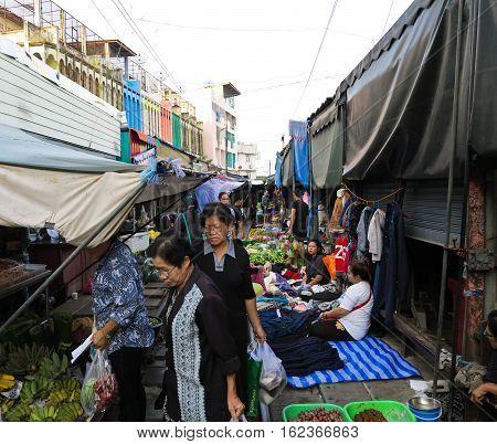 MAEKLONG, THAILAND - DECEMBER 11, 2016: The famous railway market or folding umbrella market at Maeklong, Thailand, A famous market in Thailand and sixth times a day the train runs through these stalls.