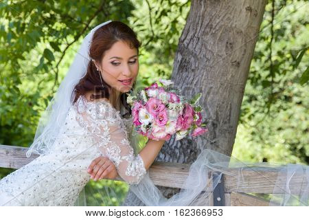 Stunning young bride posing in a green summer garden