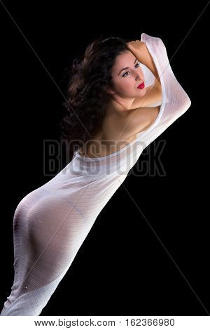 Beautiful artist model posing in a mesh net tubular piece of stretchy fabric against a black backdrop.