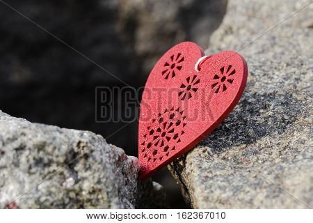 Red wooden heart symbol lying on big stone. Love consept.