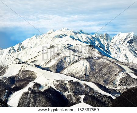 Hakuba mountain range in the afternoon early winter. The gondola and chair lifts visible are located on the top third of the mountain. The mountains massive size is noticeable against the tiny chair lifts, buildings and skiers.