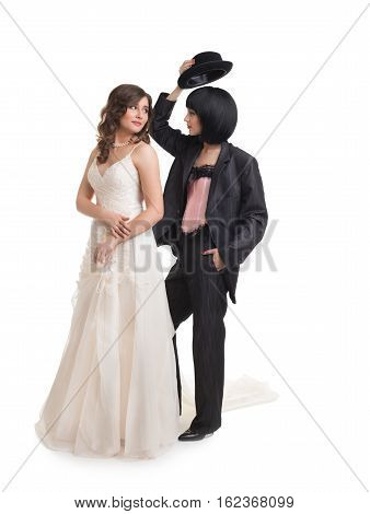 Wedding shoot. Full length of  female gay couple dressed like groom and bride standing in studioand looking at each other, isolated on white