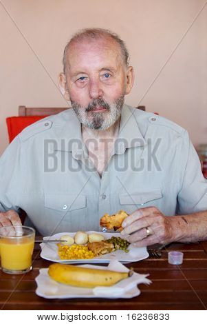 Senior man eating well balanced diet with medication tablets