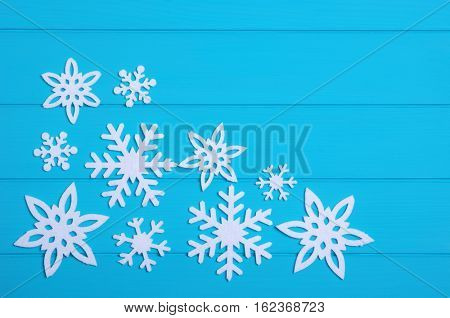 Snowflakes and stars on a blue wooden background