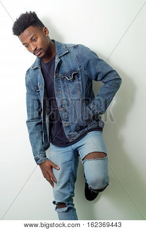 young man studio shot jeans and jacket cool relaxed and confident