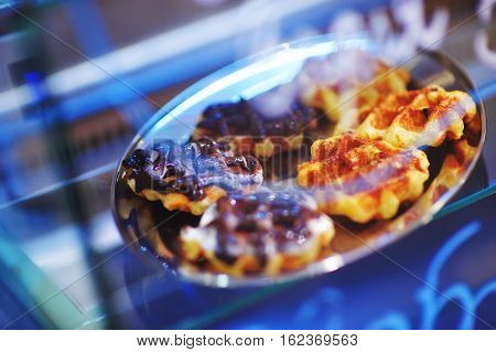 Showcase pastry shop with mouthwatering waffles with chocolate on a tray and with a beautiful neon-lit close-up.