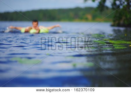Beautiful natural background. The focus of clean blue water swaying small waves on the river on blurred background of forest and sky the silhouette of a man floating on an inflatable circle