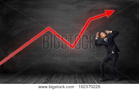 Businessman standing on floorboard and bending in fear under a bright red statistic arrow on grid background. Profit and loss. Managing business. Business statistics.