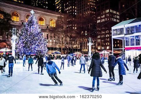 NEW YORK-DECEMBER 14: Ice skaters enjoy rink by the Bryant Park Christmas tree on December 14 2016 in Manhattan.