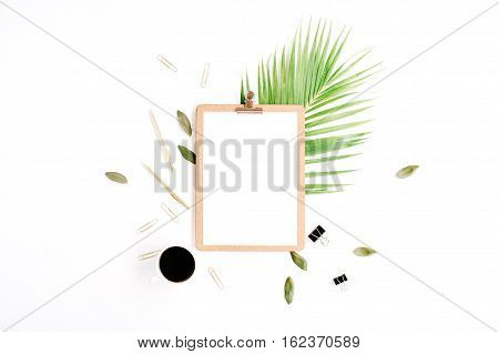 clipboard with empty copy space blank coffee mug golden pen and clips petals and palm branch on white background. flat lay top view