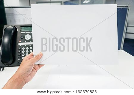 Hold mock up white paper sheet in hand with office background