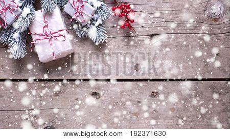 Christmas border. Wrapped christmas presents fur tree branches red berries on aged wooden background. Selective focus. Place for text. Drawn snow.