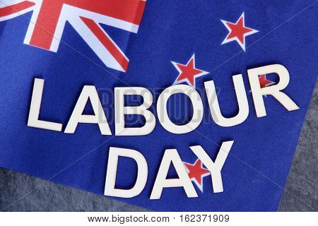 Labour Day signage with a background of the New Zealand flag.