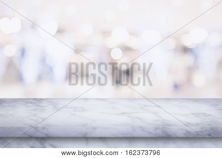 Empty white marble table with blur shopping mall background. For display or montage your products.