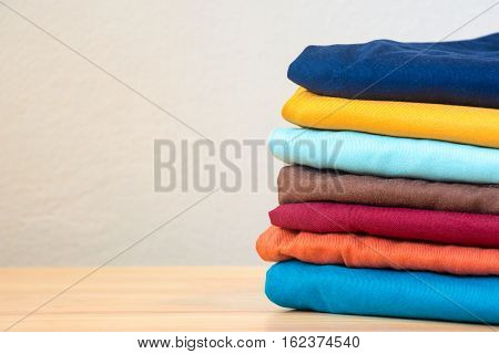 Stack of colorful clothes on wood table Housework and objects concept