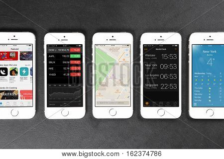 Apple iPhone 5s smartphones lying in a row on leather surface