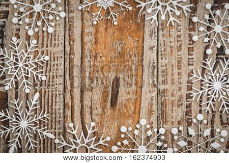 Paper snowflakes on wooden background