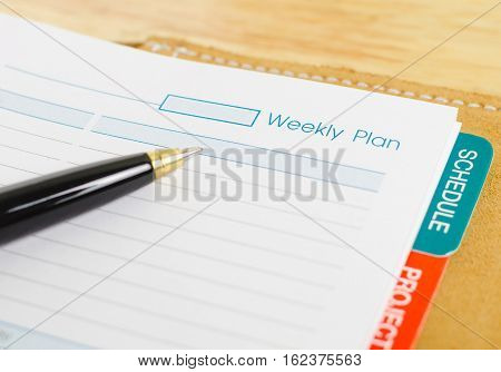 close up shot of daily notebook with pen focus on weekly plan wording business concept