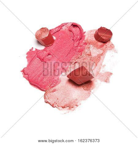 Different color samples of smeared and sliced lipstick on white textured background. Lip make-up product