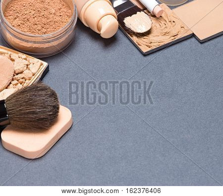 Frame of foundation makeup products with brushes and cosmetic sponges on gray background. Copy space