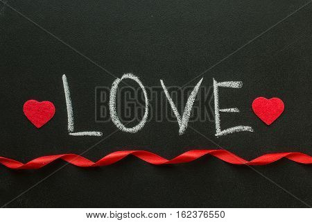 Love text written on chalkboard with a red ribbon. Valentine's Day Concept