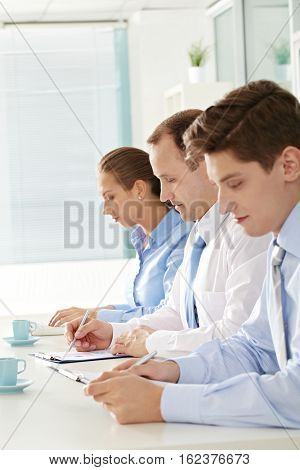 Three business people sitting in a row at seminar and writing