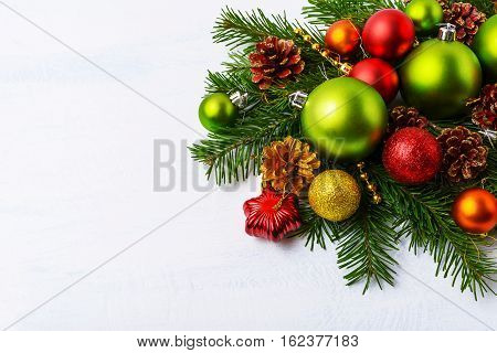 Green Christmas ornaments fir branches red star and baubles. Christmas greeting background with holidays decoration. Copy space.