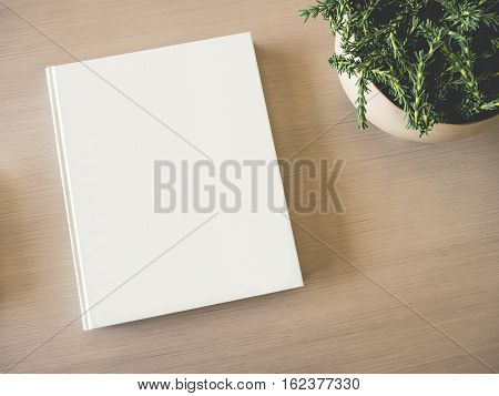 Mock up Book Cover on table with Green Plant wooden background