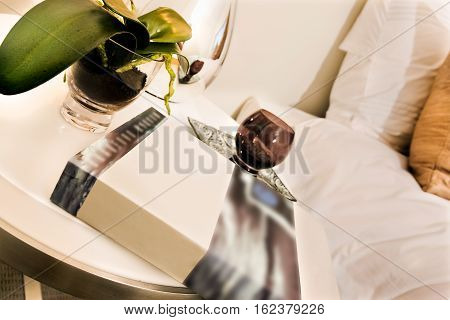 Close view of a book on the table it may be a novel near to a tiny brown glass on a plate. There is a green color ornamental plant and background is blurred in the bedroom