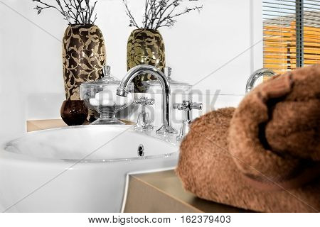 Modern silver color washstand is curved and fixed to the white ceramic sink. The brown wool towel is blurred on the counter front of the mirror. There is a dark colored glass next to the fancy vase and glass bowl including Cotton balls
